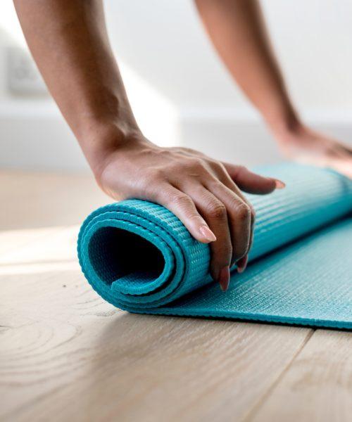 Bilde av ei som ruller sammen yogamatten